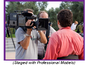 Professionally staged photo with professional models depicting cameraman with interviewee.