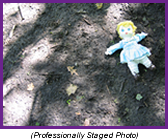 Child's doll laying in the dirt on a shadowed forest floor (Professionally Staged Photo).