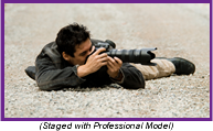 Photographer laying on the ground shooting a picture with a long lens camera (Staged with Professional Model).