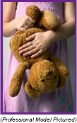 Young girl in pink dress clutching her teddy bear (Professional Model Pictured).